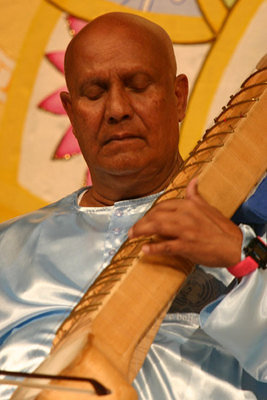 Sri Chinmoy is in deep meditation while playing the instruments