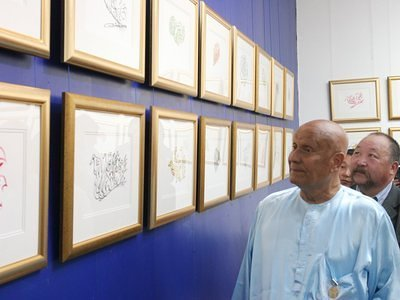 Sri Chinmoy is looking at his paintings